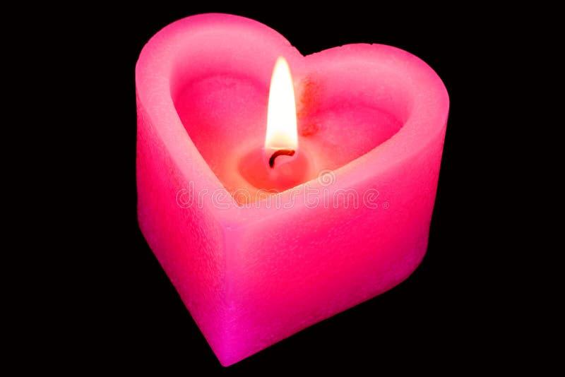 Hjärta formade den brännande stearinljuset på svart royaltyfri bild