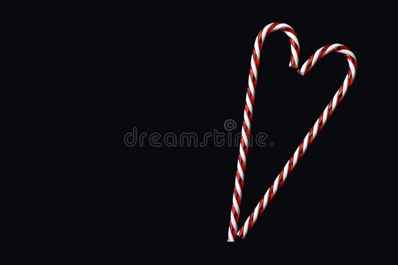 Hjärta formade den röda och vita randiga traditionella julgodisrottingen på svart bevekelsegrund för bakgrundshälsningkort royaltyfri foto