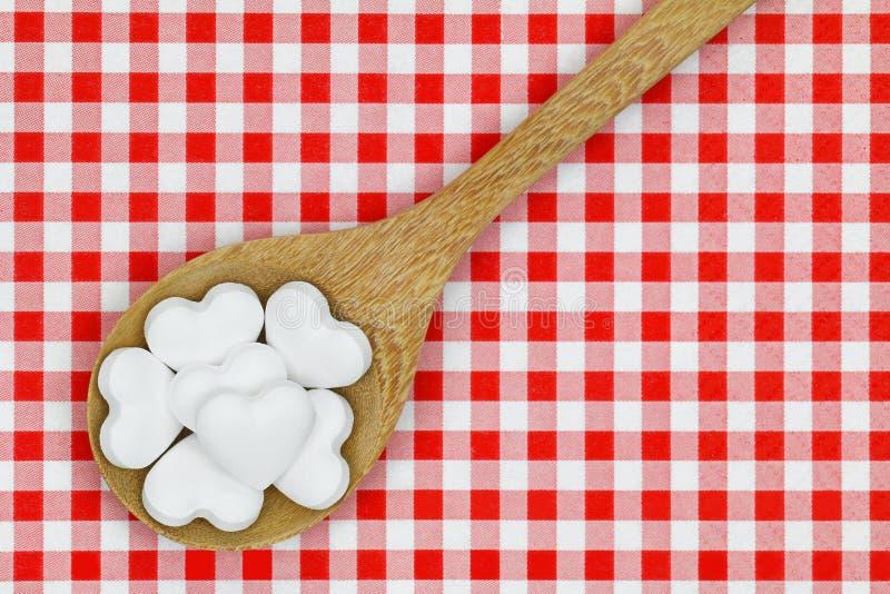 Hjärta formade godispreventivpillerar på rutig bakgrund för röd gingham royaltyfri fotografi