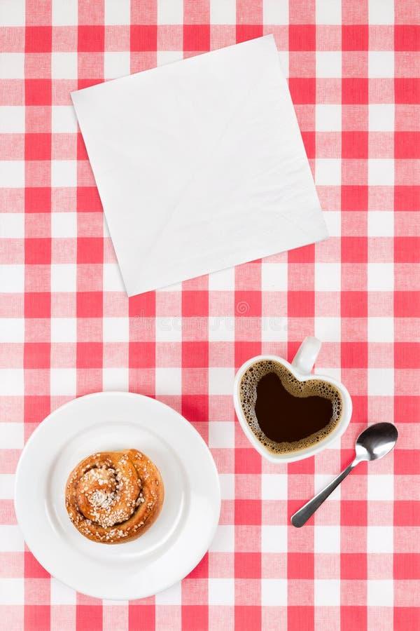 Hjärta formade kaffekoppen och en kanelbrun bulle arkivfoton