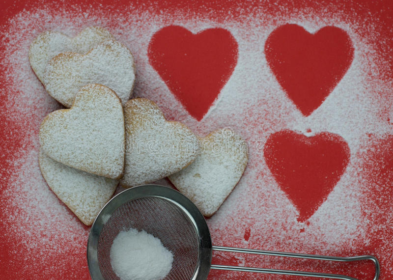 Hjärta formade kakor med sockerpulver för valentins dag arkivbild