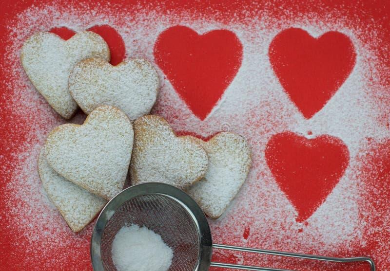 Hjärta formade kakor med sockerpulver för valentins dag arkivfoton