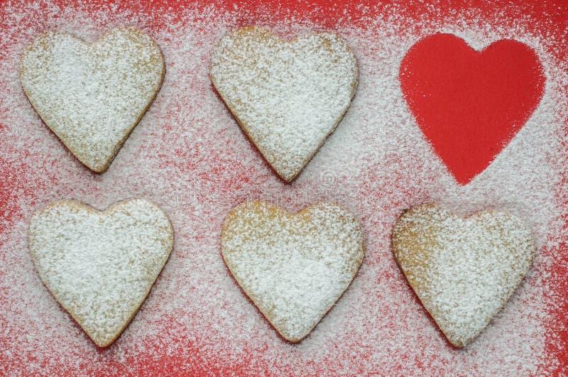 Hjärta formade kakor med sockerpulver för valentins dag arkivfoto