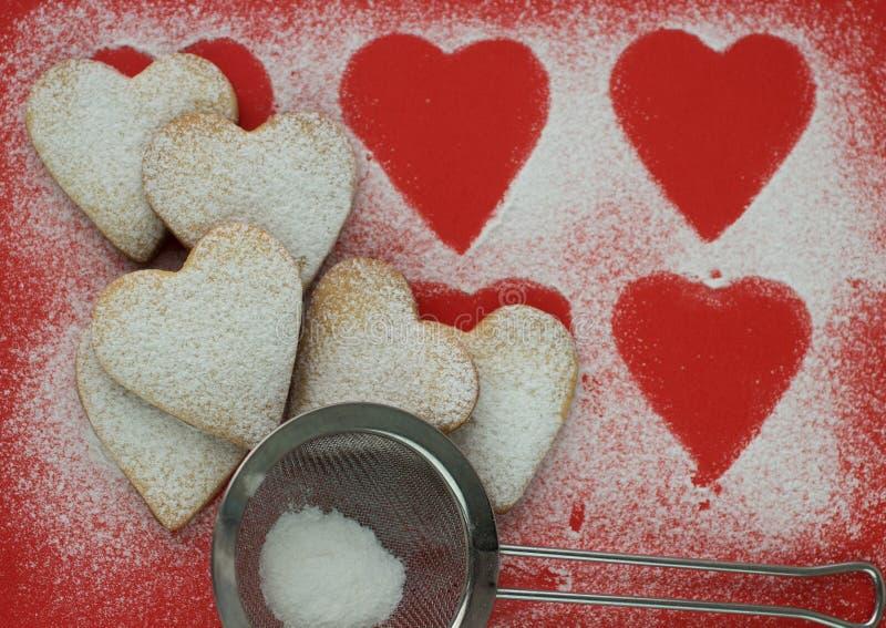 Hjärta formade kakor med sockerpulver för valentins dag arkivbilder