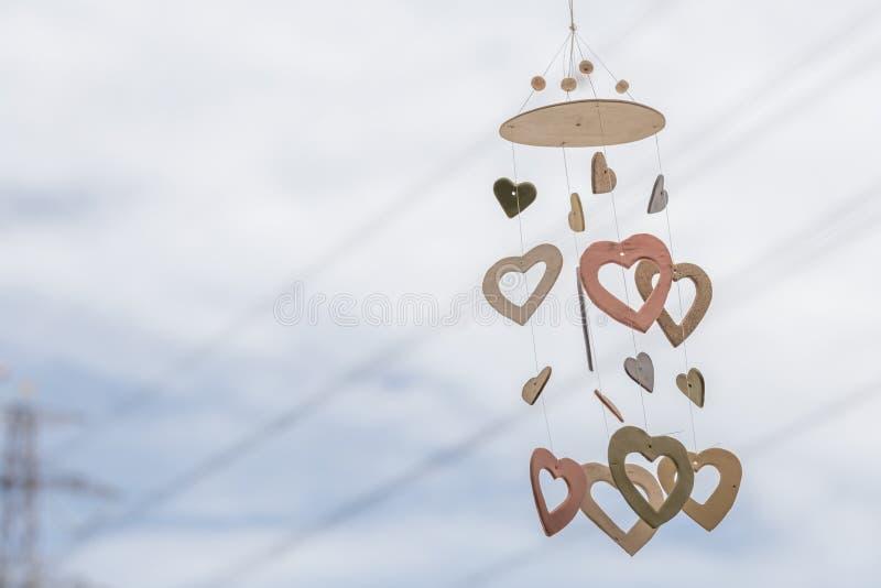 Hjärta formade keramiska defocused vindchimes som hänger på fönster och royaltyfri foto