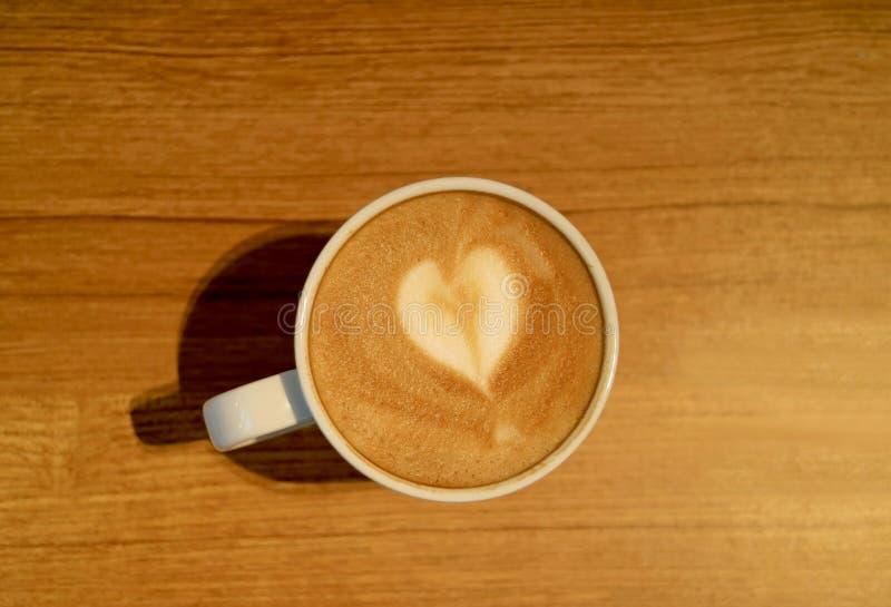 Hjärta formade Lattekonst av varmt cappuccinokaffe med Lattekonst i en vit kopp som tjänades som på trätabellen royaltyfri bild