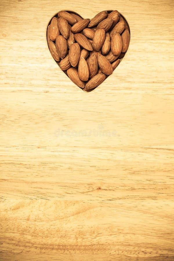 Hjärta formade mandlar på träyttersidabakgrund royaltyfri fotografi