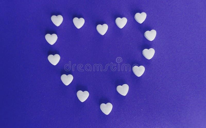 Hjärta formade minnestavlor på purpurfärgad bakgrund arkivfoton