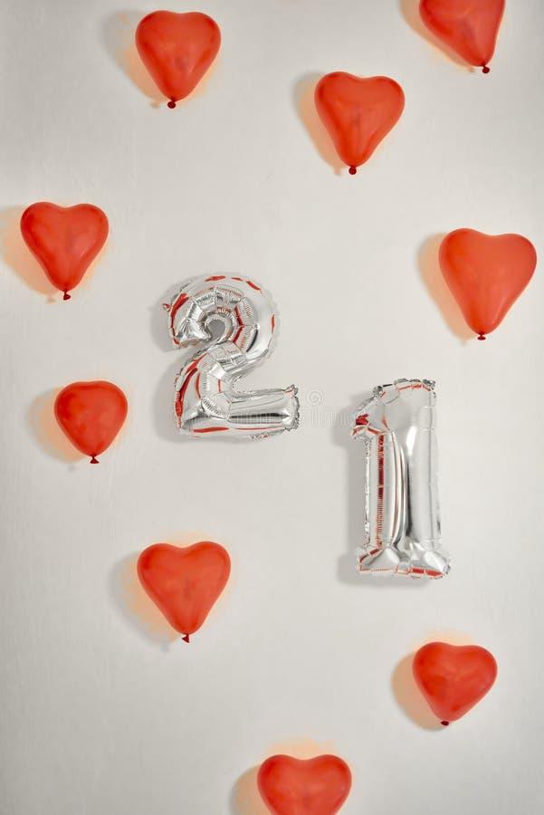 Hjärta formade röda ballonger och numrerar 21 ballonger på vit bakgrund royaltyfria foton