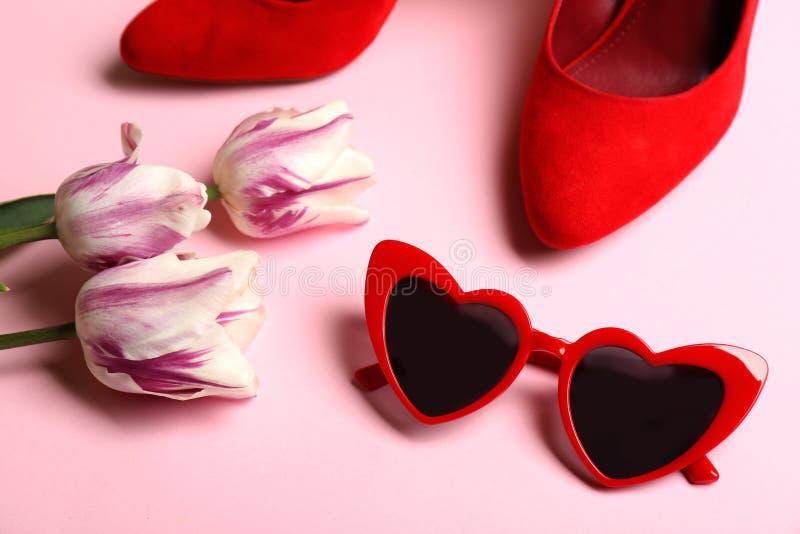 Hjärta formade solglasögon, skor och tulpanblommor arkivbild