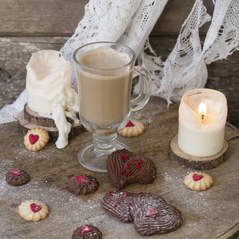 Hjärta formade wienska choklad- och vaniljvalentins kakor för dag med en exponeringsglaskopp kaffe med mjölkar på en träbakgrund royaltyfri fotografi