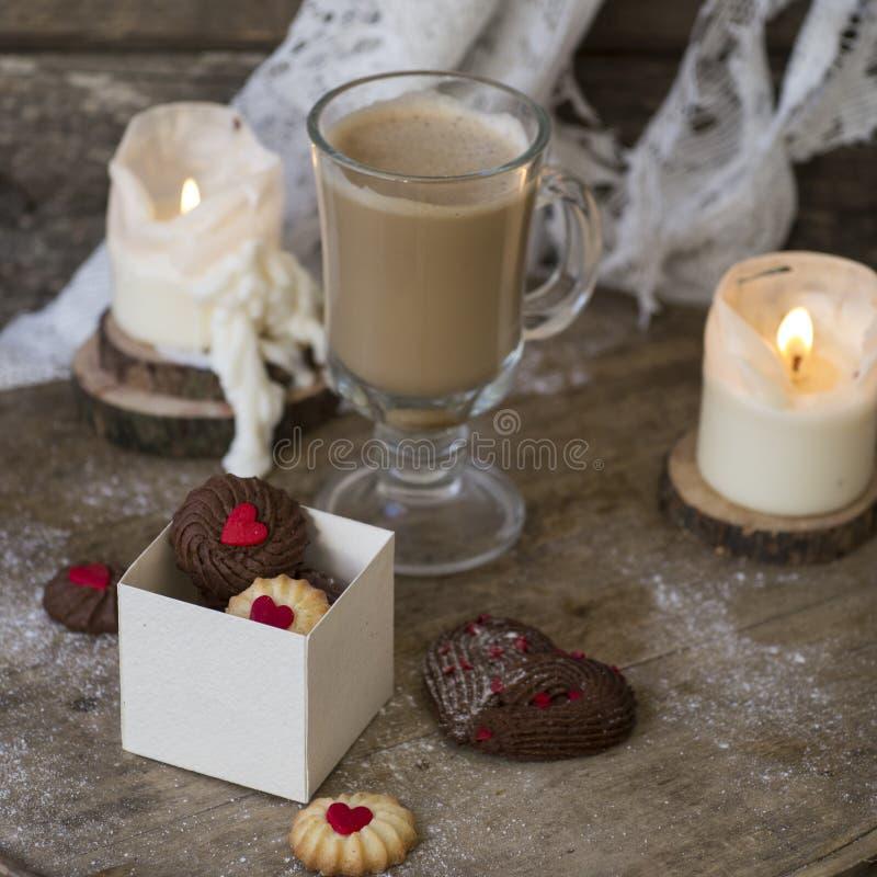 Hjärta formade wienska choklad- och vaniljvalentins kakor för dag med en exponeringsglaskopp kaffe med mjölkar på en träbakgrund arkivbild