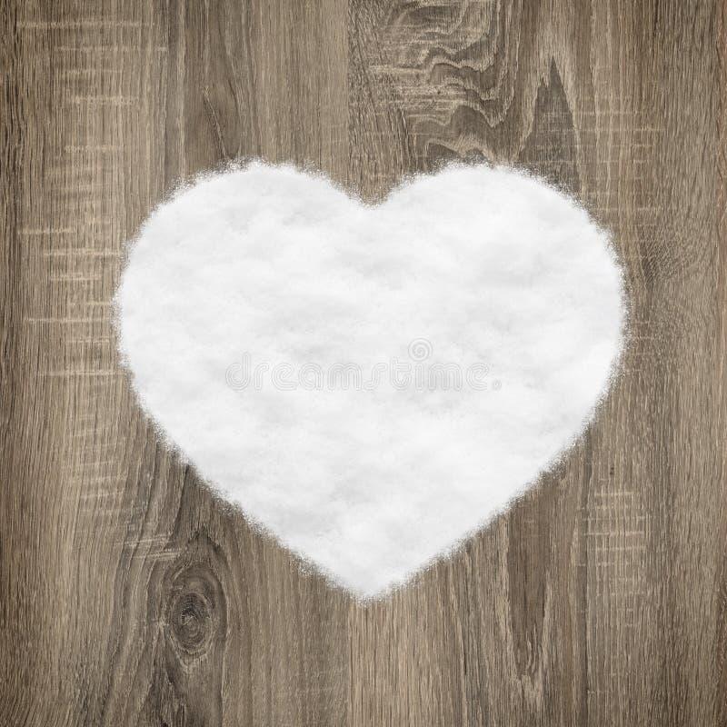 Hjärta formar gjort av trä och snow arkivbild