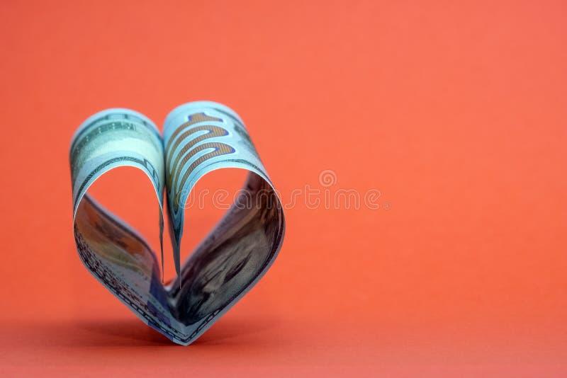 Hjärta från hundra dollarräkningar USA på en röd bakgrund Begrepp av pengar, förälskelse och en gåva för valentin dag kopiera avs royaltyfria foton