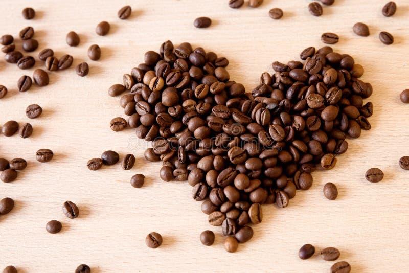 Hjärta från kaffebönor på wood textur arkivfoto