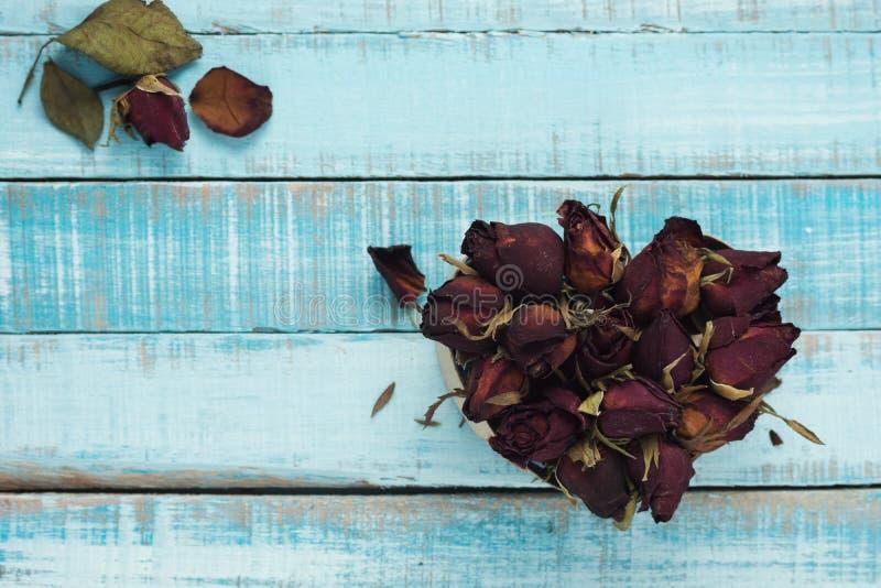 Hjärta från torkade rosor på blåa parkettplankor royaltyfria bilder