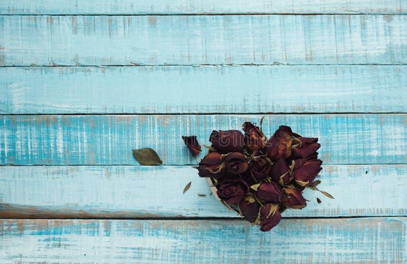 Hjärta från torkade rosor på blått trä royaltyfria foton