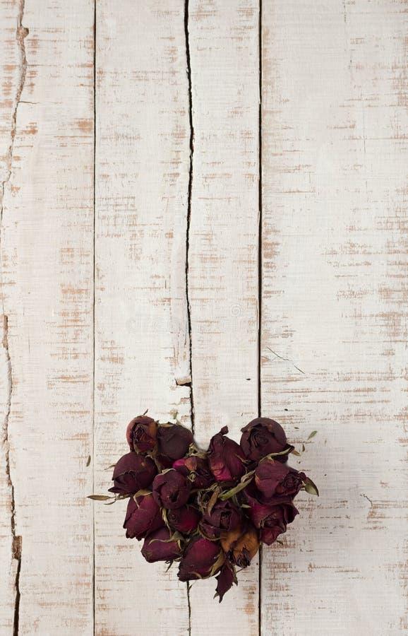 Hjärta från torkade rosor på träparkettplankor royaltyfri foto