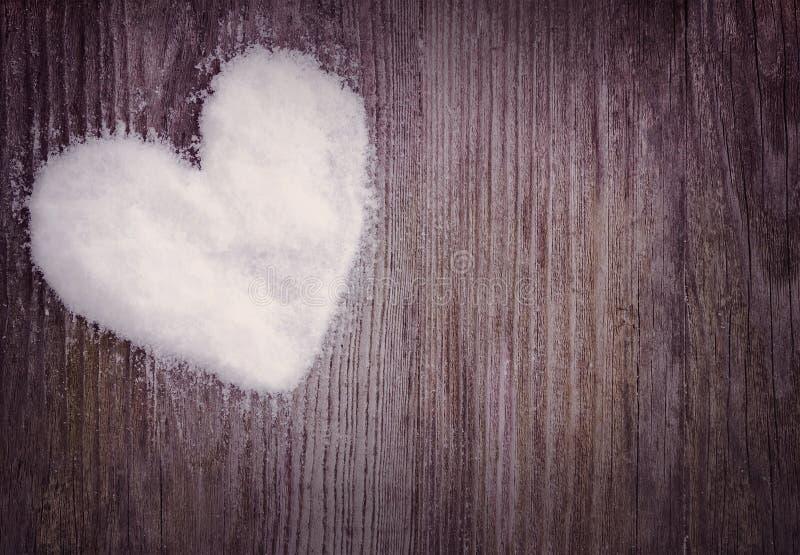 Hjärta gjorde av snö på en träbakgrund royaltyfria foton