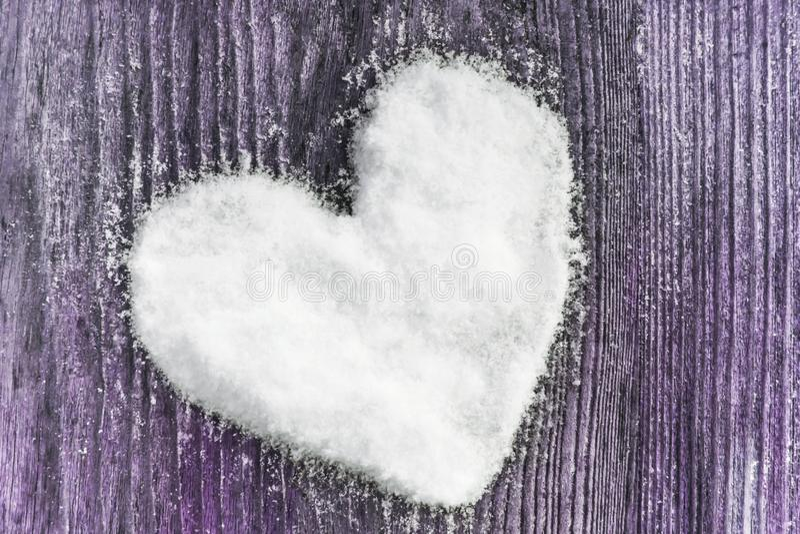 Hjärta gjorde av snö på en träbakgrund royaltyfri bild