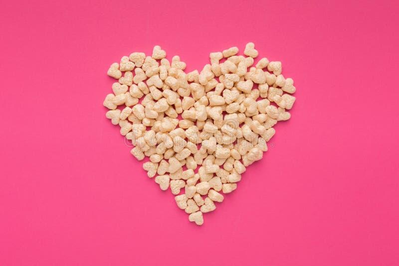 Hjärta gjorde sädesslag på en rosa bakgrund royaltyfri foto