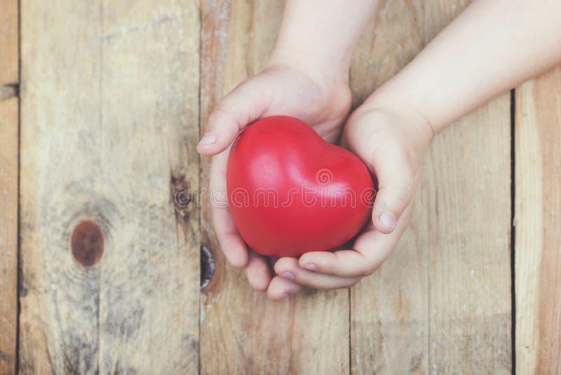 Hjärta i händer för barn` ett s arkivfoto