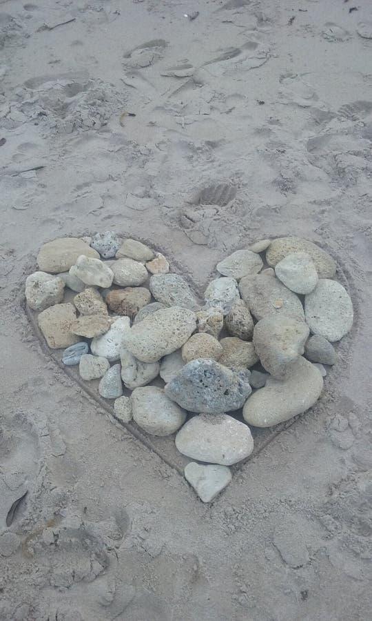 Hjärta i sanden vaggar korallstranden arkivbilder