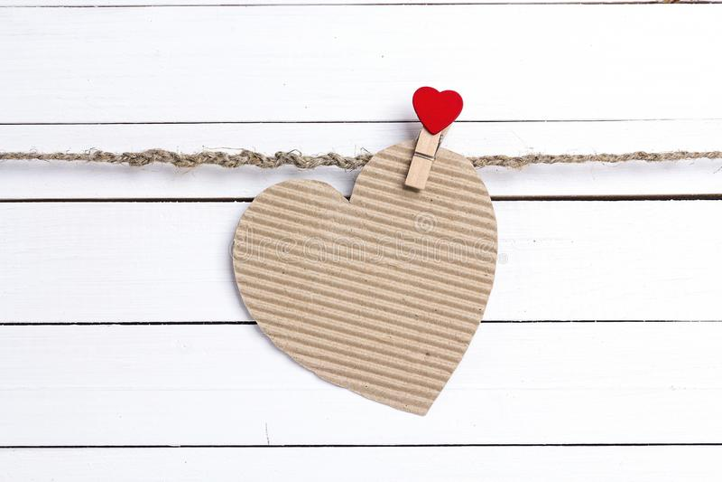 Hjärta-kort för tomt papper som hänger på klädnypor på vita trälodisar arkivfoton