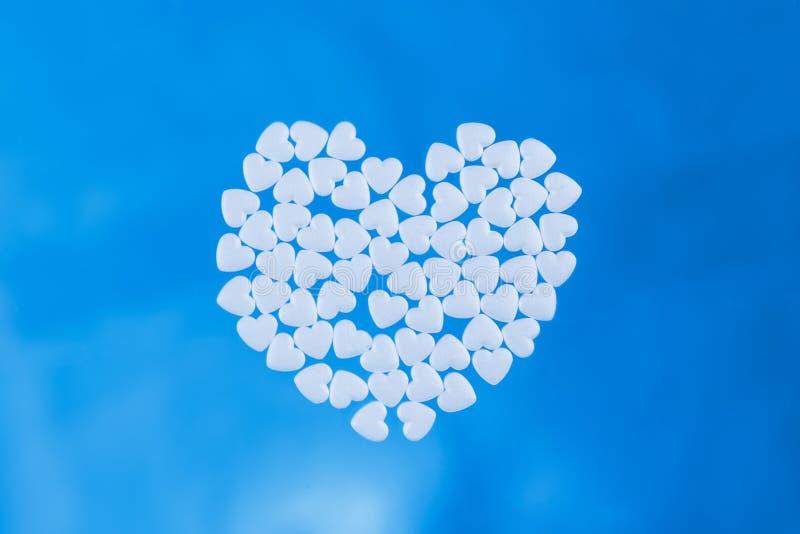 Hjärta lade ut från minnestavlor i form av hjärtor på en blå bakgrund arkivfoton