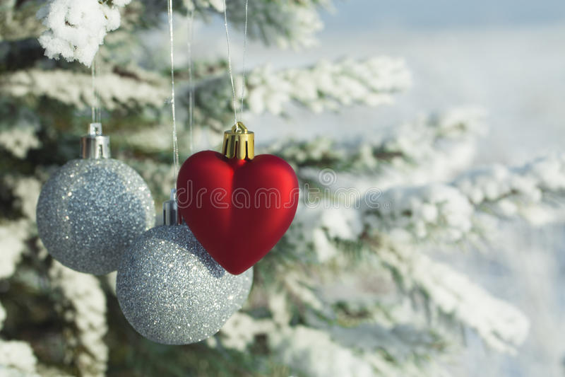 Hjärta leker med silverbollar på en sörjafilial i den snöig skogen royaltyfri fotografi