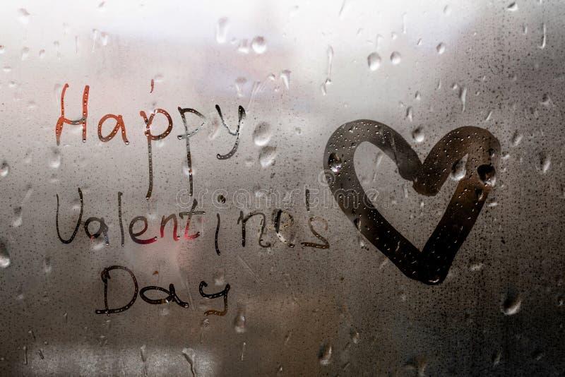 Hjärta målad lycklig valentindag för inskrift på fönster i regnigt väder arkivfoto
