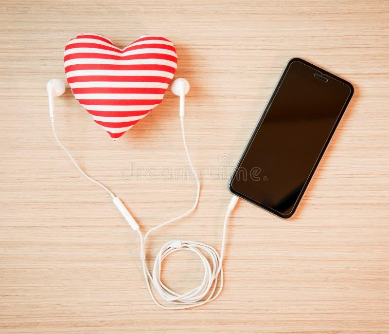Hjärta med smartphonen och hörlurar arkivfoton
