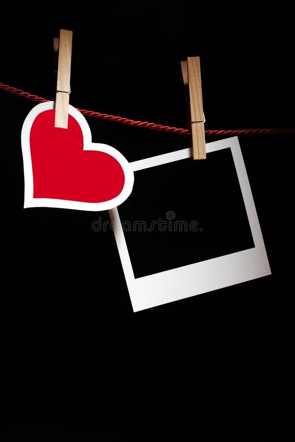 Hjärta och fotoet inramar arkivfoton