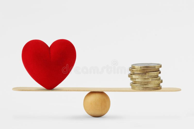 Hjärta och pengar på jämviktsskalan - beställning av prioriteten i liv bland förälskelse och pengar arkivbild