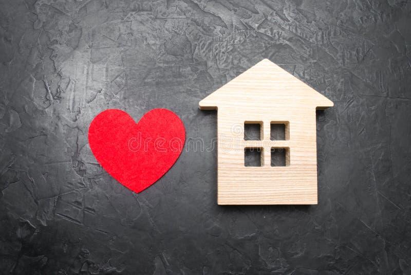 Hjärta och trähus på en grå konkret bakgrund Begreppet av ett förälskelserede, sökandet för nytt som man har råd med hus för barn royaltyfria bilder