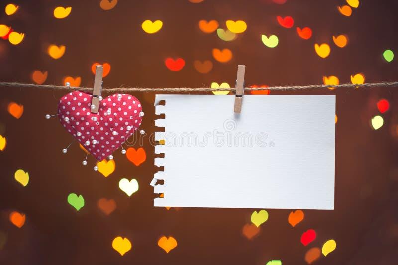 Hjärta och visare med anmärkningen på klädstreck hjärta för gåvan för dagen för begreppet för den blåa asken för bakgrund isolera fotografering för bildbyråer