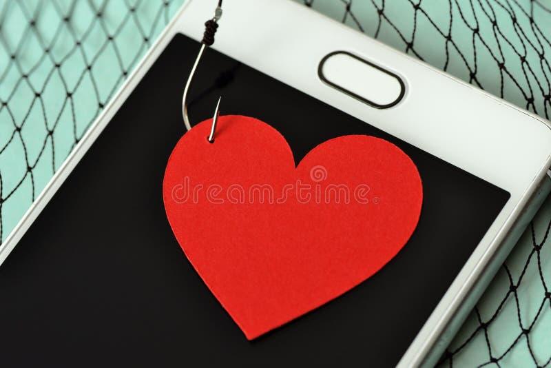 Hjärta på fiskkroken på mobiltelefonen och fisknät - förälskelsebegrepp royaltyfria bilder