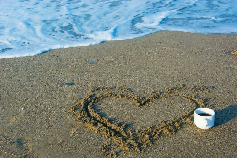 Hjärta på sanden nära havet arkivfoton