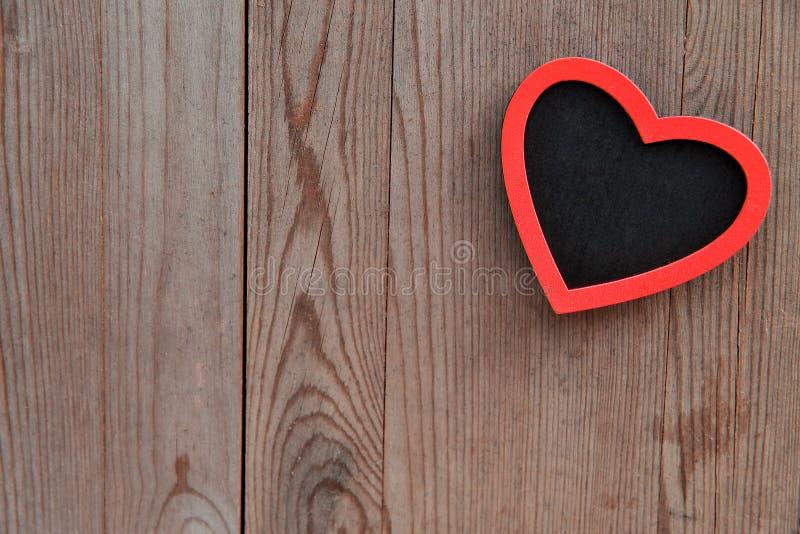 Hjärta på träbakgrund, valentin daggarnering arkivfoto
