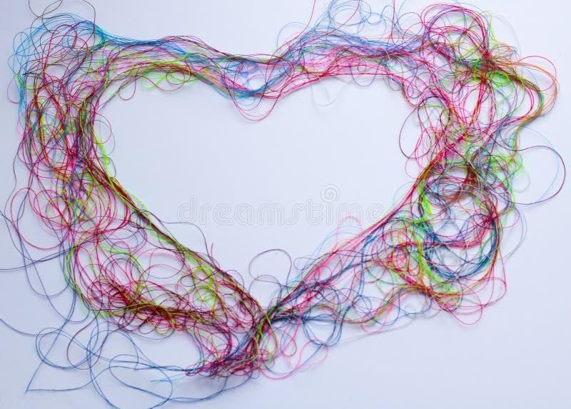 Hjärta - ram av den färgrika sömnadtråden - hjärtaform, kopieringsutrymme och bakgrund royaltyfria foton