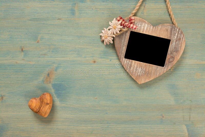 Hjärta ram på det svarta fotoet Valentindag på den lantliga träväggen med kopieringsutrymme royaltyfri bild