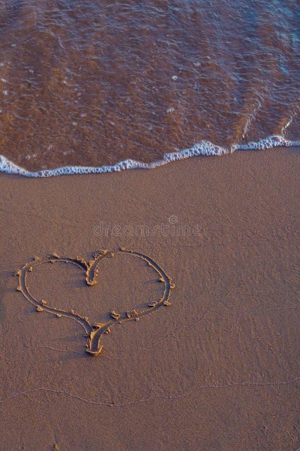 Hjärta som är skriftlig på sand på stranden royaltyfria foton