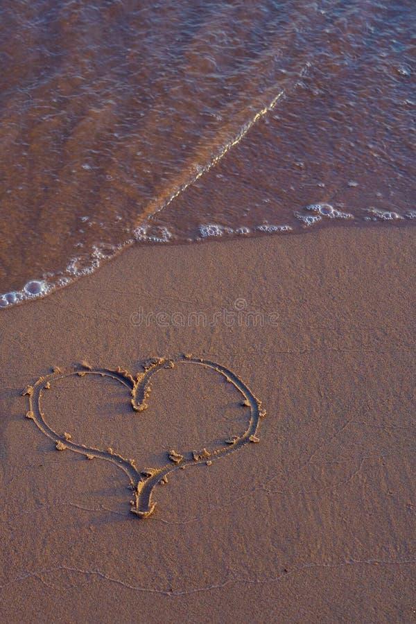 Hjärta som är skriftlig på sand på stranden fotografering för bildbyråer