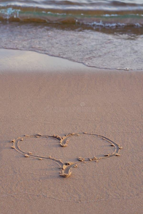 Hjärta som är skriftlig på sand på stranden arkivbild