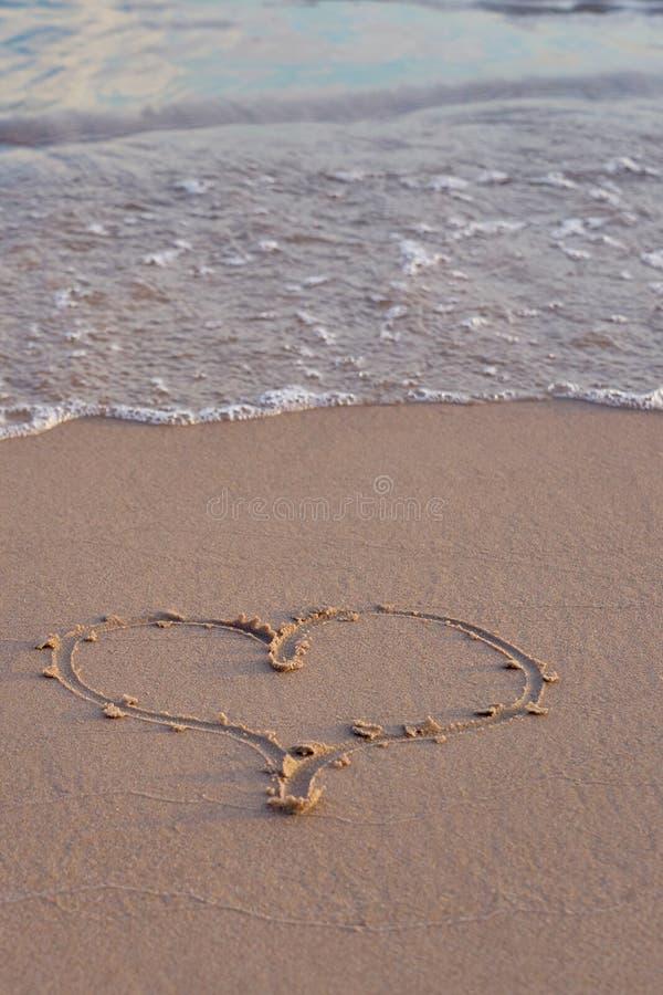 Hjärta som är skriftlig på sand på stranden arkivfoton