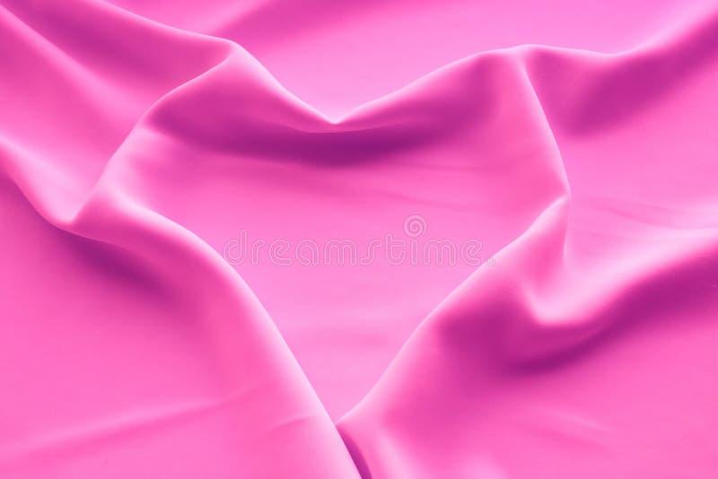 Hjärta som draperar på rosa tygsilke arkivbild