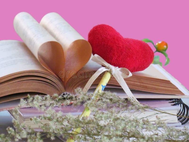 Hjärta som formas som göras av sidor för gammal bok med röd isolerade hjärta för bokmärke och torkade blommor på rosa bakgrund Be royaltyfri bild