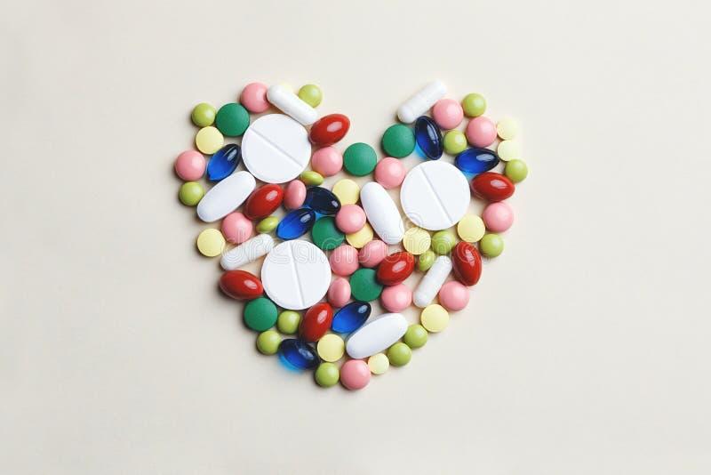 Hjärta som göras av blandade mång--färgade piller royaltyfri bild