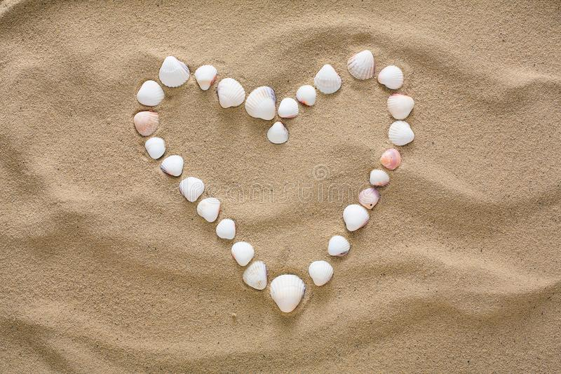 Hjärta som göras av havsskal och kiselstenar royaltyfria bilder