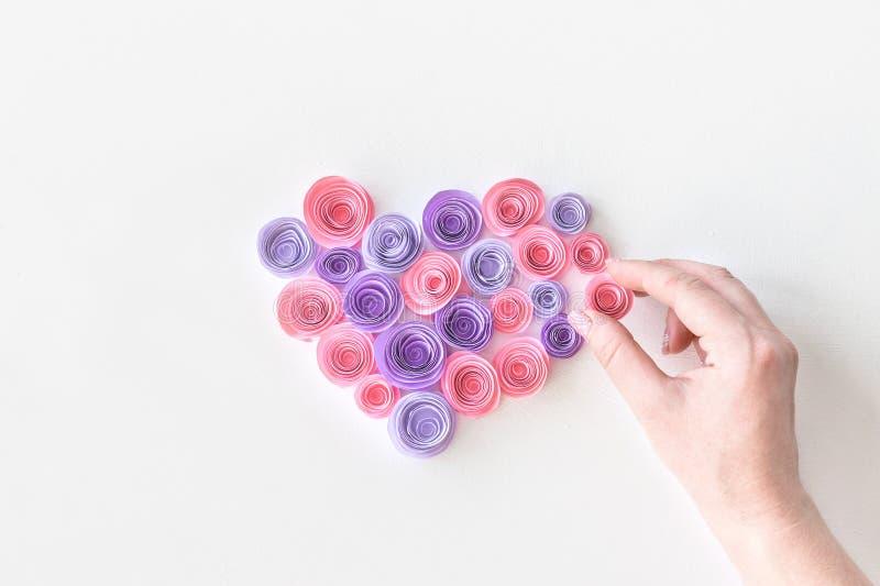 Hjärta som göras av pappers- rosa färg- och lilablommor med handen för kvinna` s Den kvinnliga handen sätter en blomma i hjärtafo royaltyfria bilder